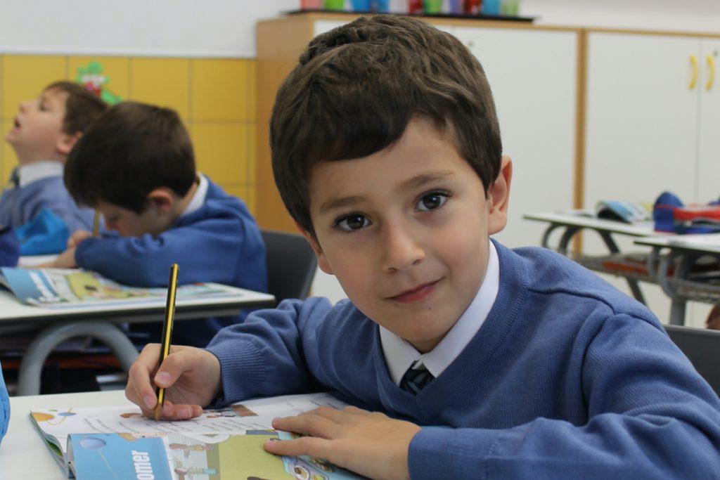"""Imagen de niño escribiendo en su pupitre para ilustrar la sección """"Tarfias"""" dentro de """"Matrículas"""""""